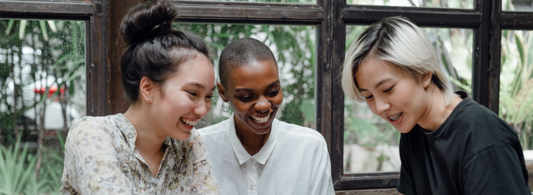 Three students in a coffee shop laughing