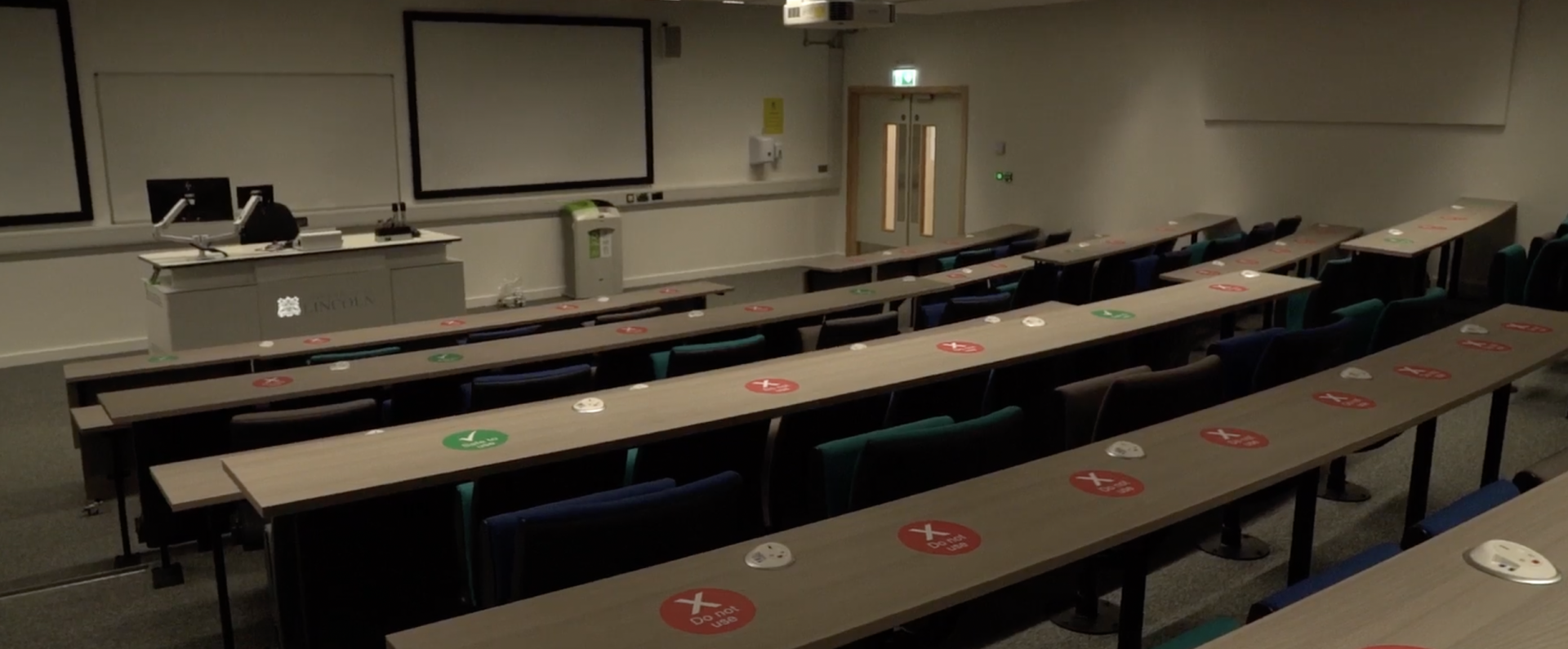 Medical building lecture hall. Shows rows of seating facing a blank projector screen.