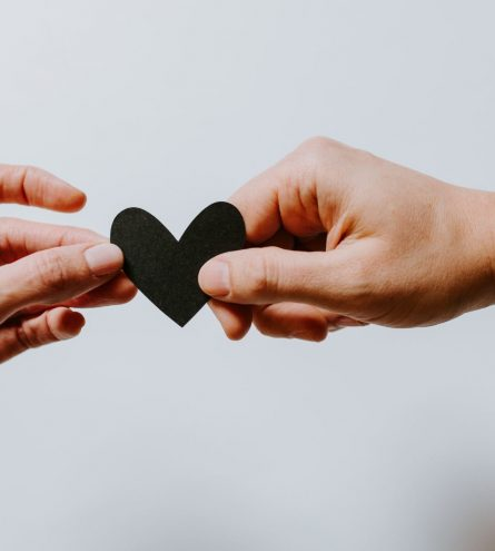 Two people holding a paper heart