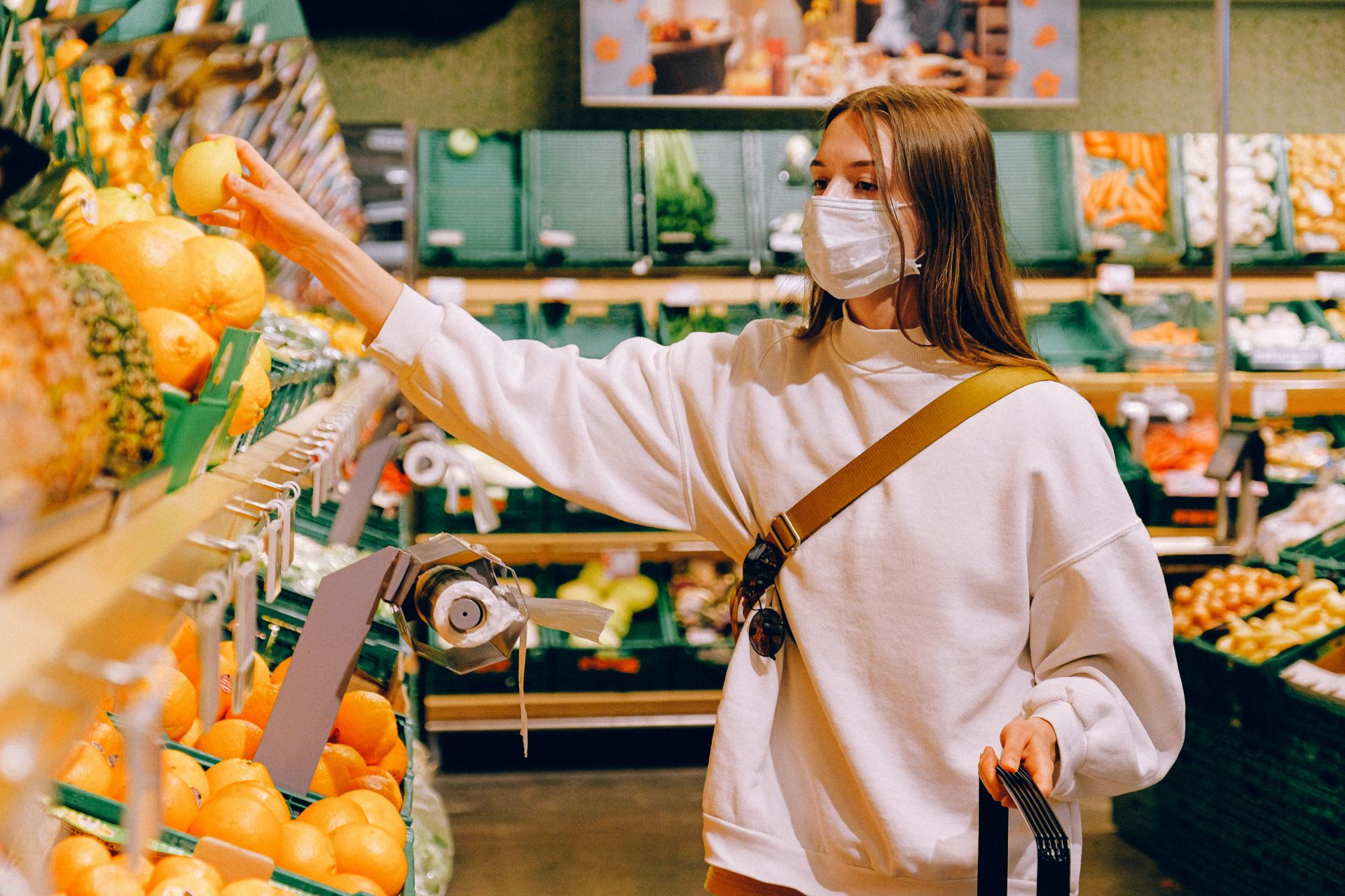 Woman wearing a mask in the supermarket buying fruit