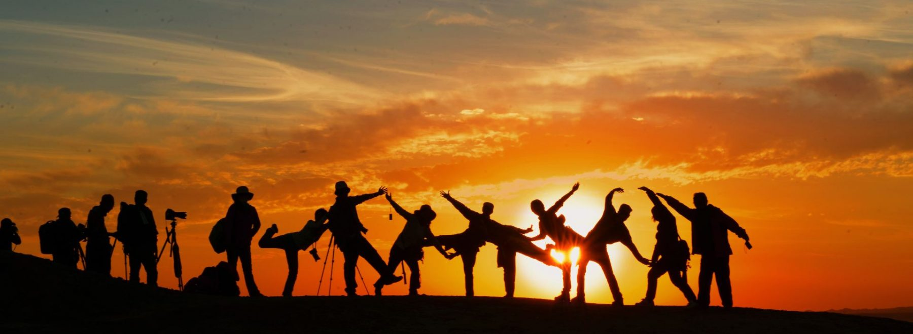 A group of people taking part in yoga in the sunset