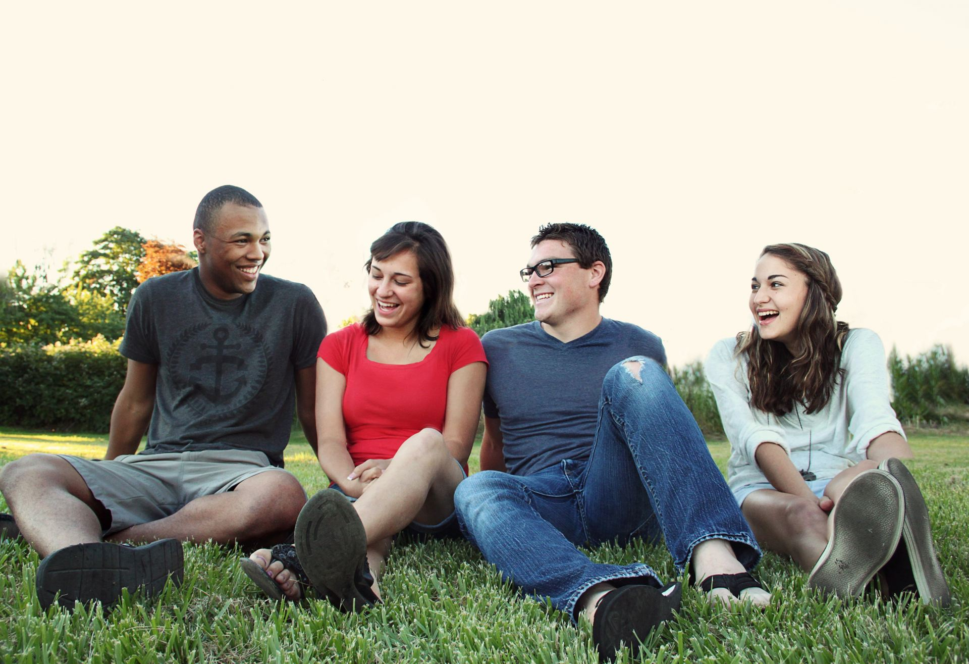 Four people sat together outside smiling