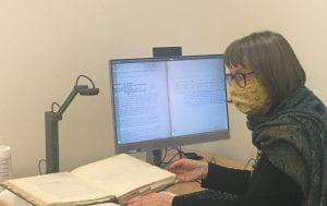 Image shows an archivist scanning a manuscript