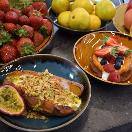 fruit and selection of multi coloured bowls with sweet potatoes filled with passion fruit, strawberries and blueberries