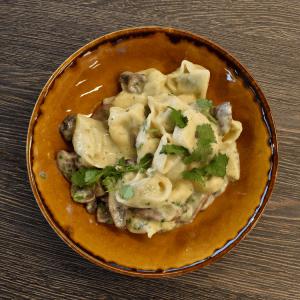 spinach mushroom ravioli covered in mushroom sauce in an orange bowl