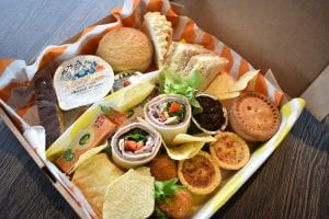 buffet box filled with a selection of savoury wraps, crisps and sweet cakes