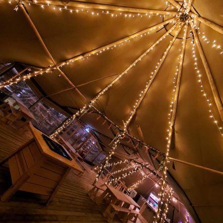 Inside view of tipi with beams with twinkly lights on