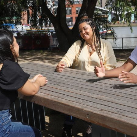 Three students sitting at a bench by a marina talking and smiling.