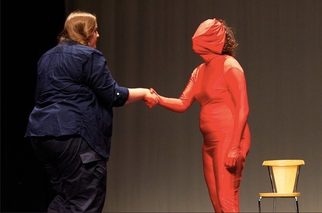 Two performers, one in a red morph suit shaking hands.