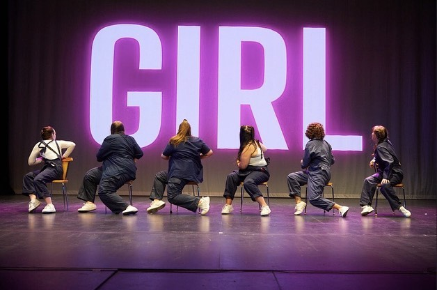 6 performers sat on chairs in front of large pink 'Girl' facing away from audience.