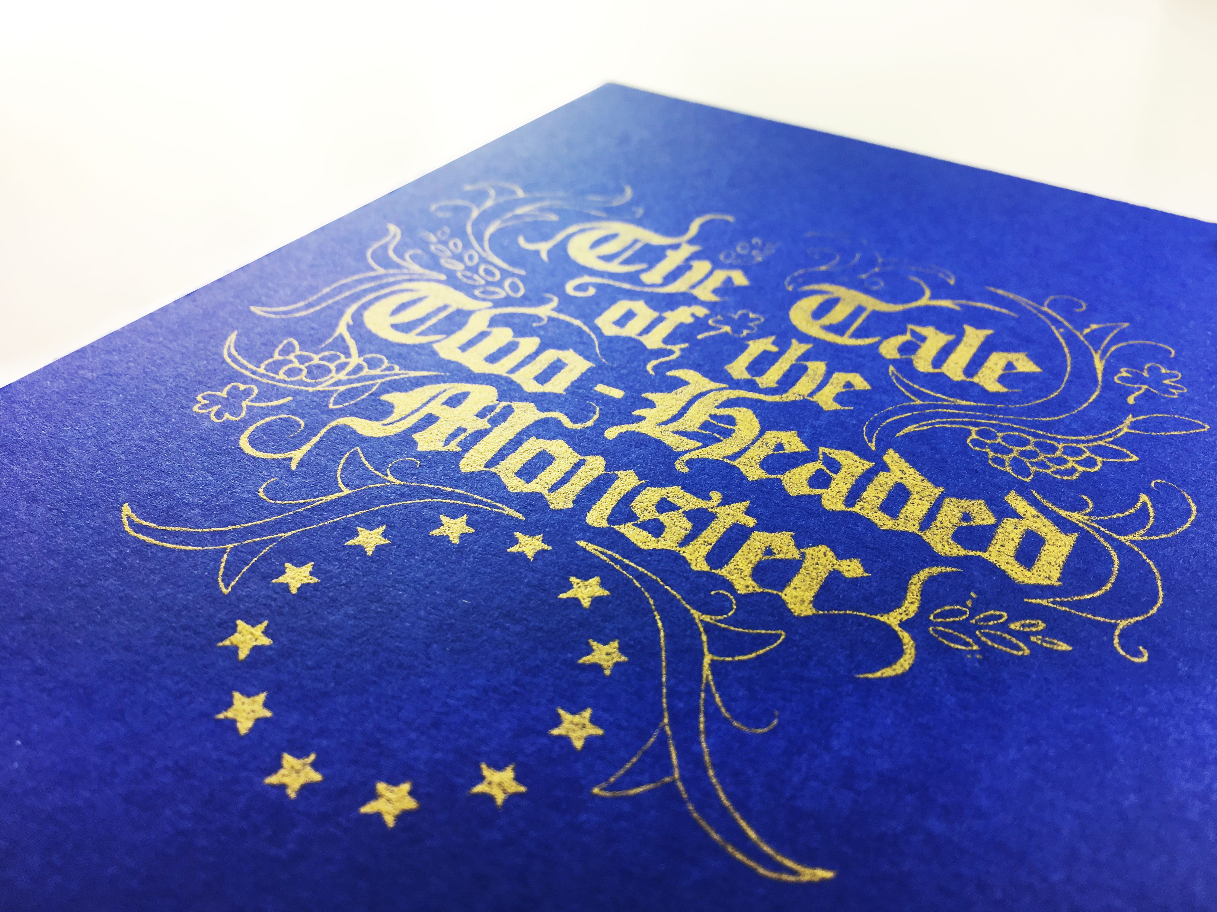 A deep-blue box, with the flag of the European Union under calligraphy text reading: 'The Tale of the Two Headed Monster.'