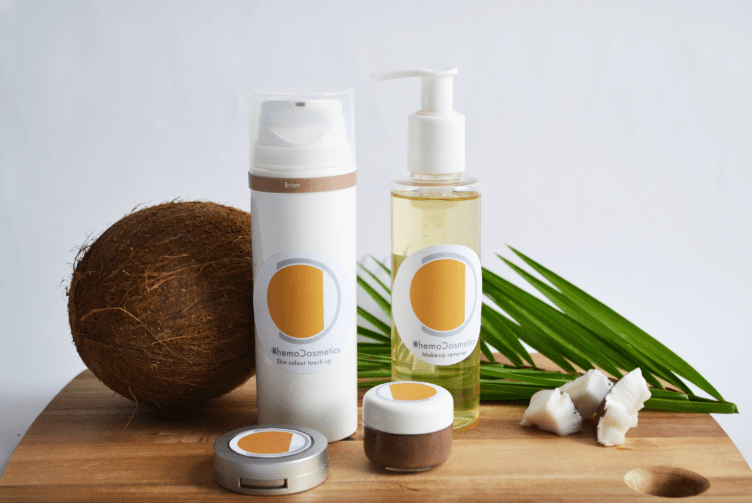 Make-up remover, blusher and eyebrow pomade from the ChemoCosmetics range, accompanied on a table by a coconut andMake-up remover, blusher and eyebrow pomade from the ChemoCosmetics range, accompanied on a table by a coconut and a palm frond.