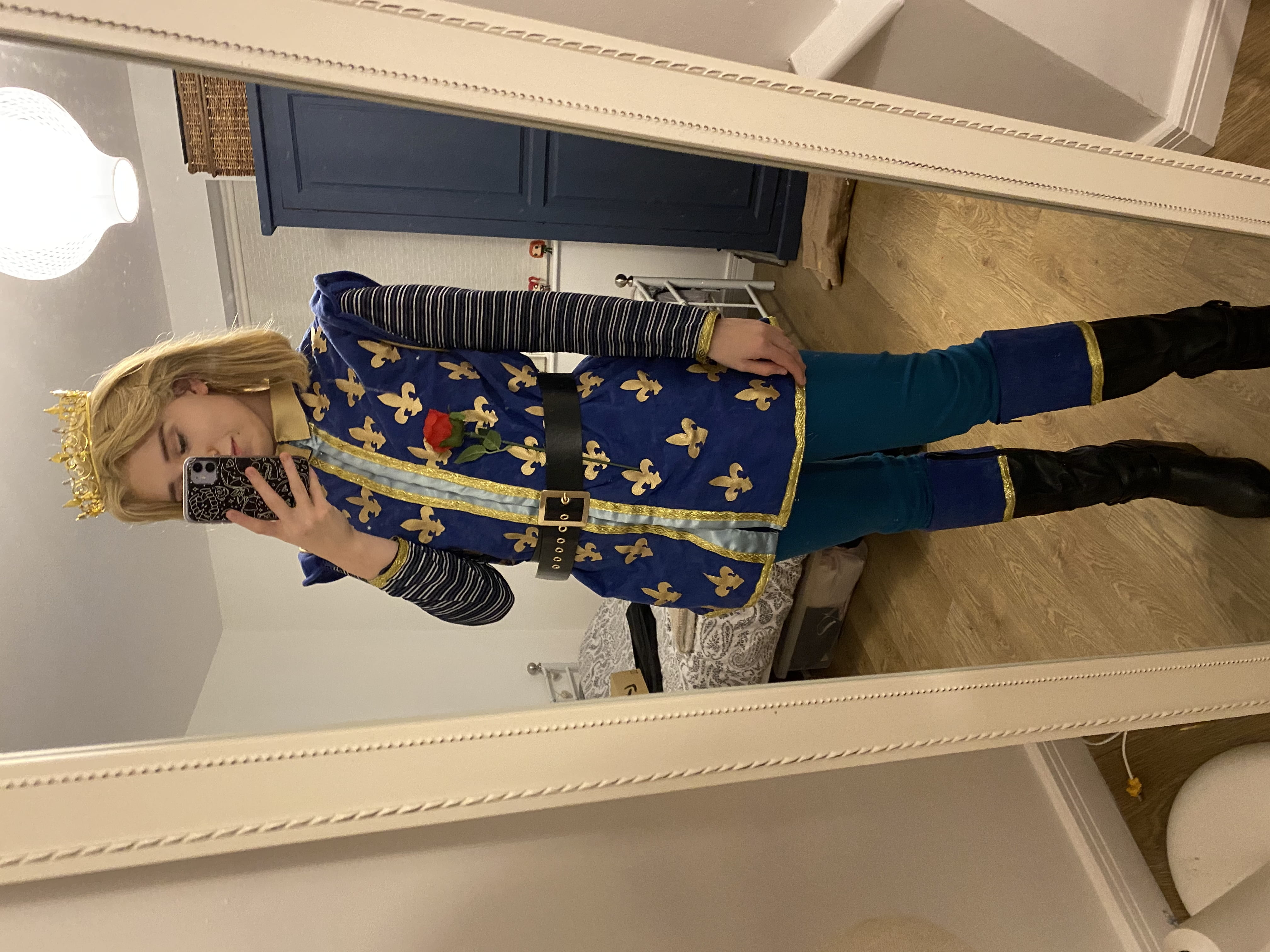 Full image of the blonde wig and gold crown, blue and gold bodice, blue leggings, black boots with a blue and gold trim and a black belt. A fake rose is tucked into the belt.