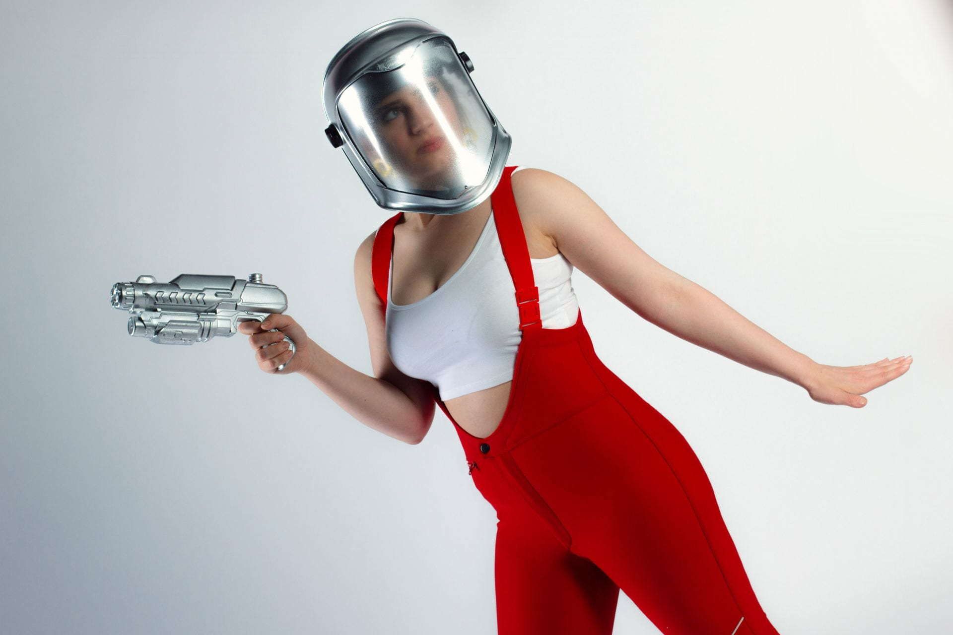 A woman in red dungarees and wearing a gas-mask, holding up a silver laser-gun.