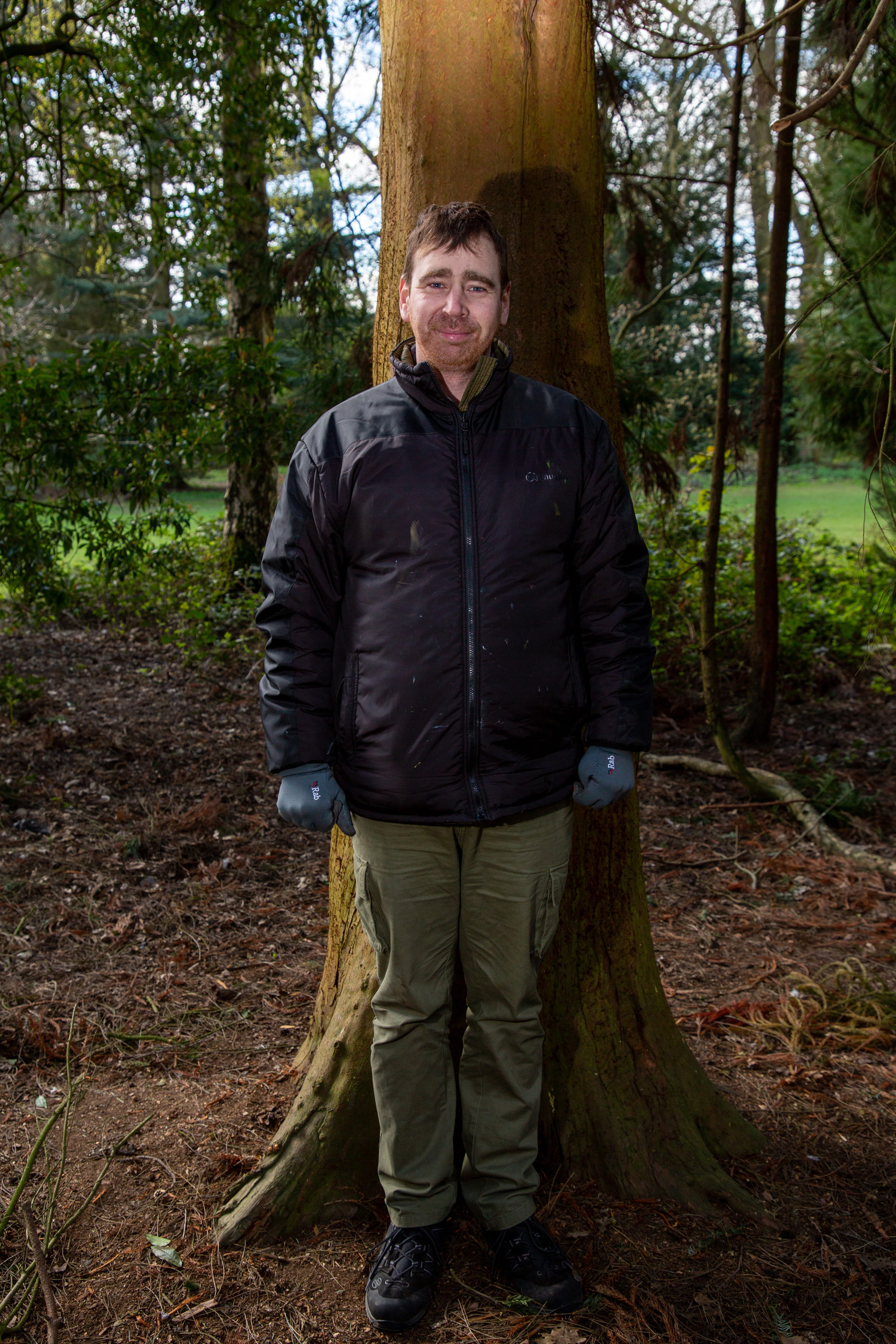 Photograph of veteran standing to attention in wooded area.