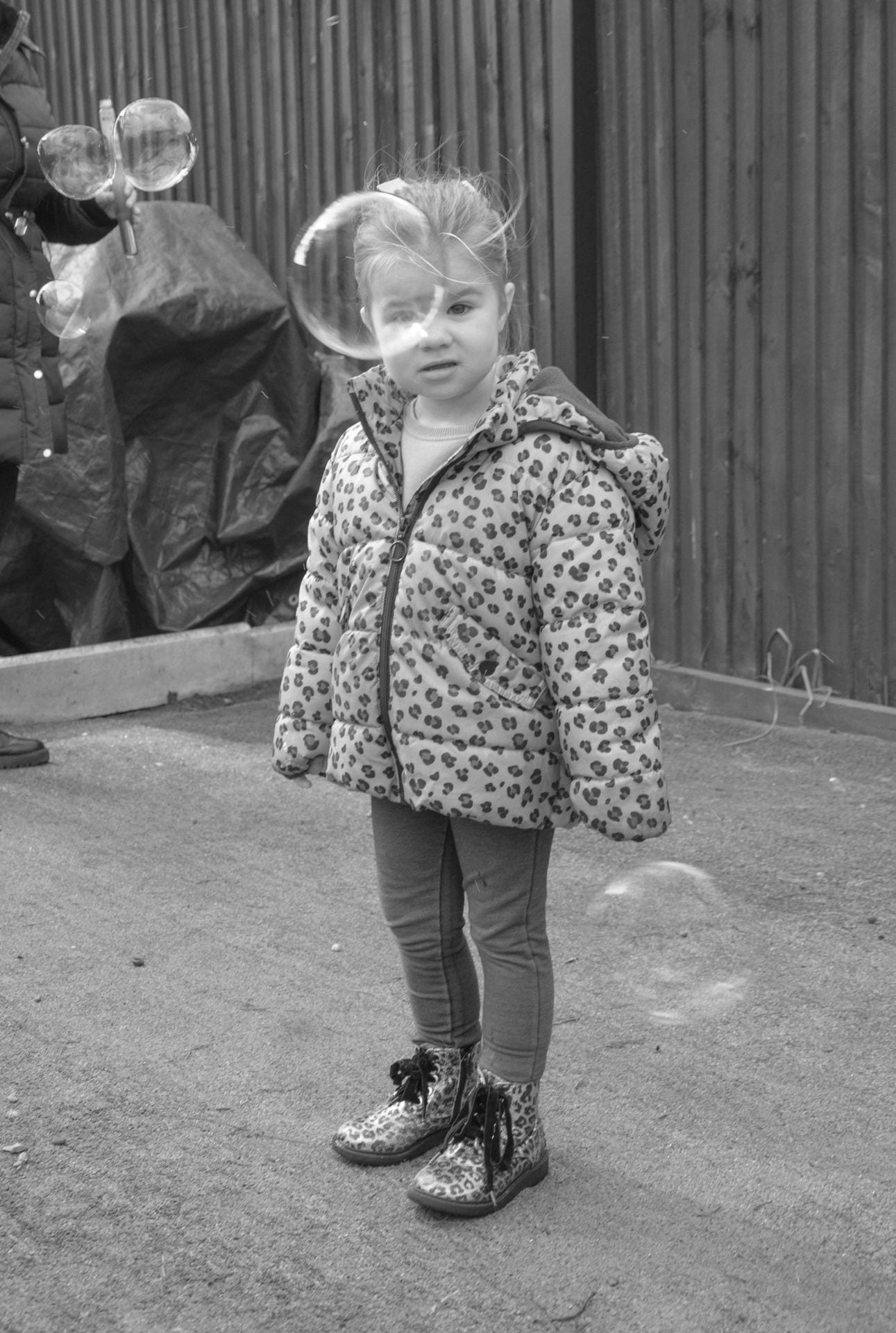 Black and white photograph of a bubble in front of a child's face.