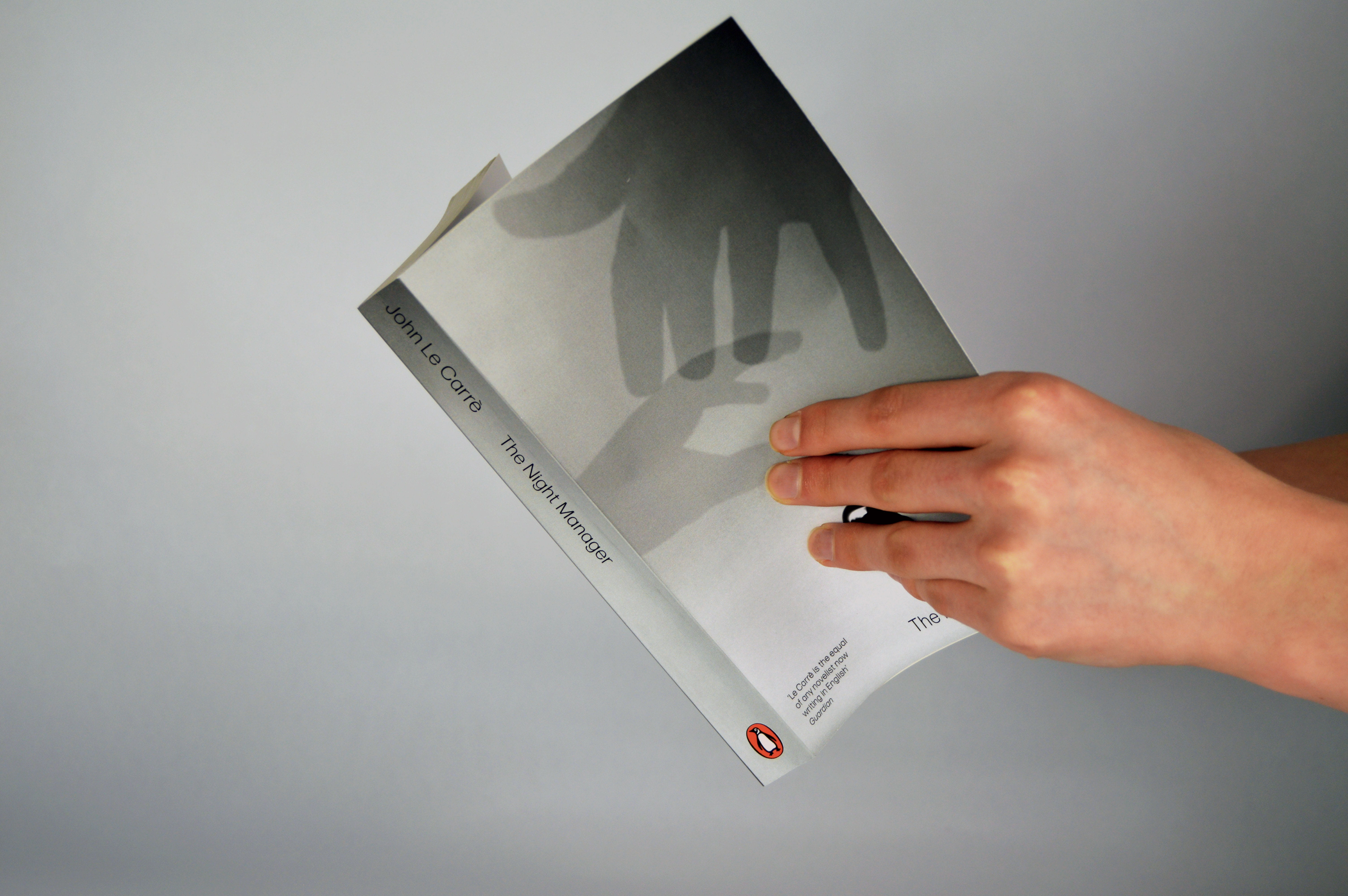 Book with front and spine visivle depicting the artwork of 2 hands reaching for the receptionists bell, and a spine matching the colour of the front cover background.