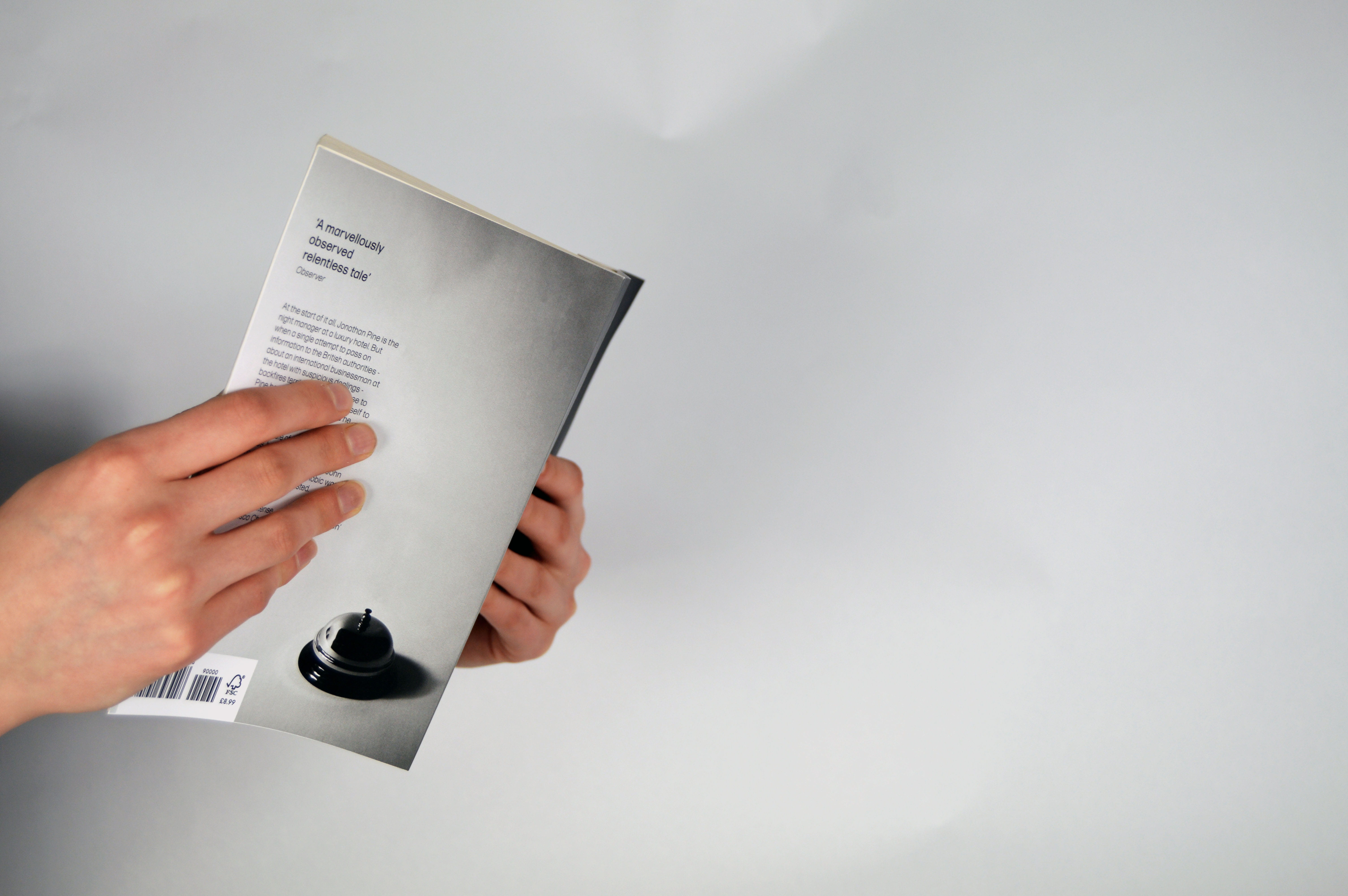 The book being held showing the back cover, this contains the blurb and an image of a receptionists bell by itself.