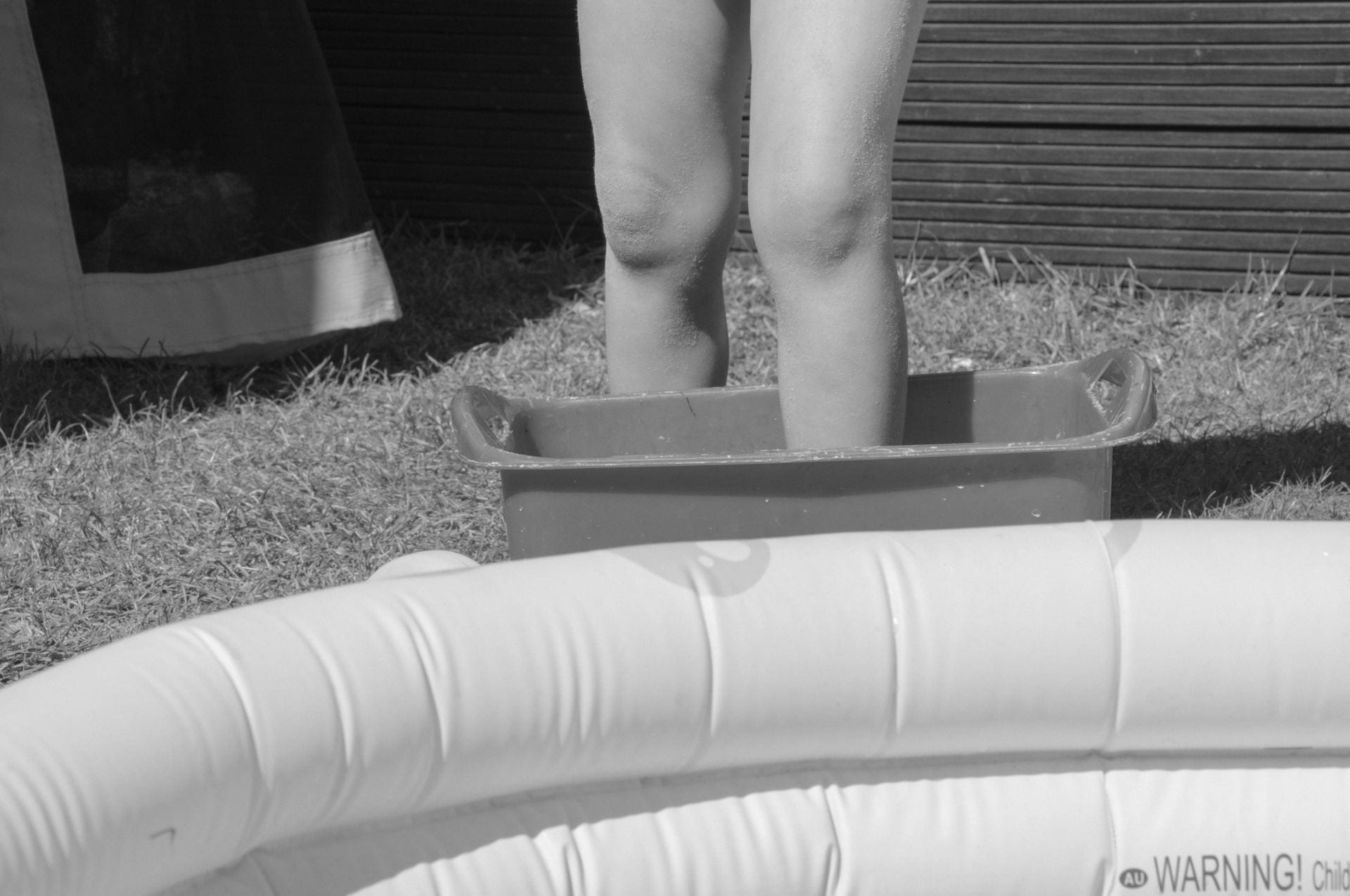 Black and white photograph of a child by a paddling pool.