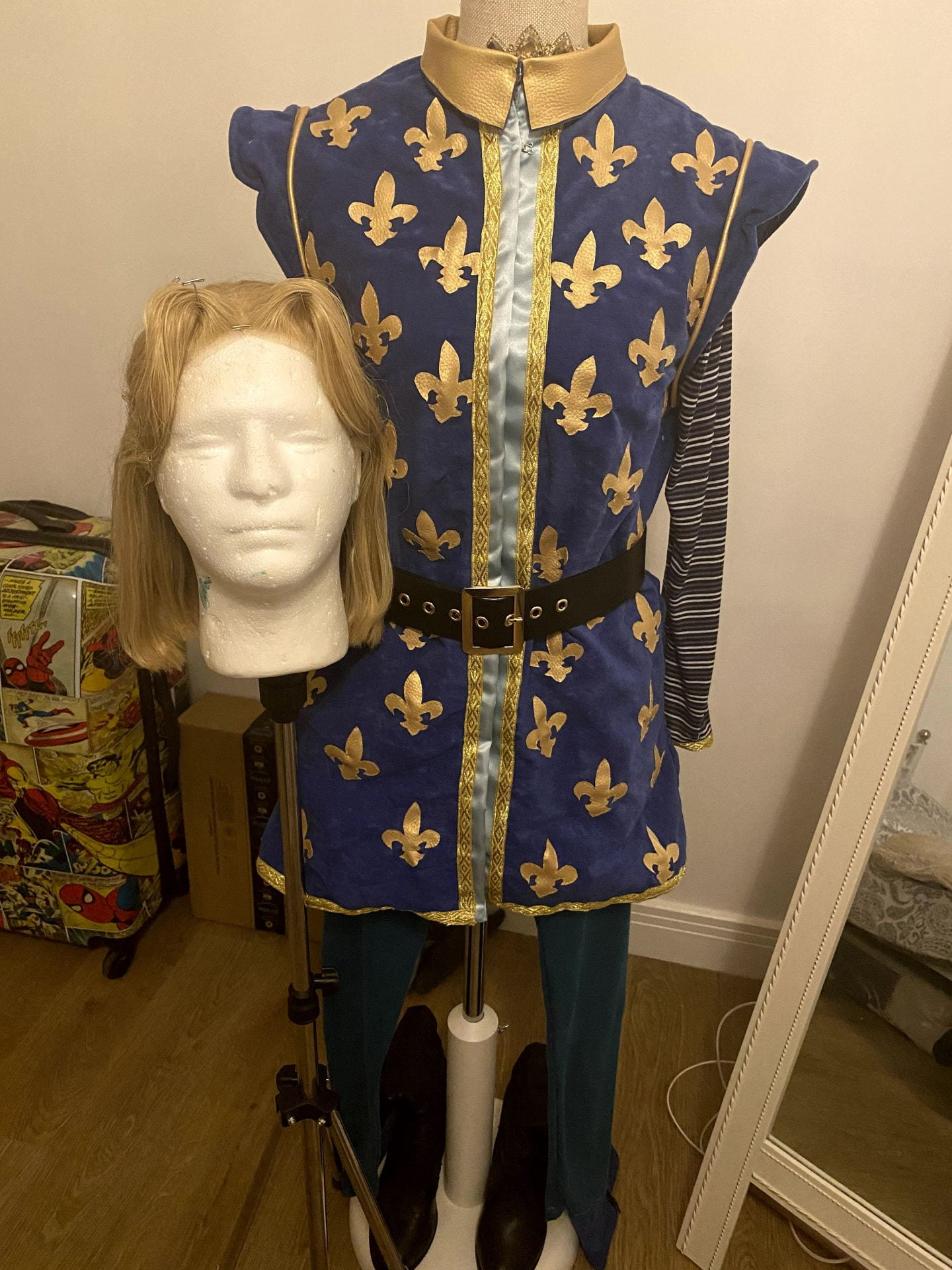 Full look at the price charming costume. Includes blonde wig, main blue bodice with gold detailing, blue leggings, black boots with a blue and gold trim and a black belt.