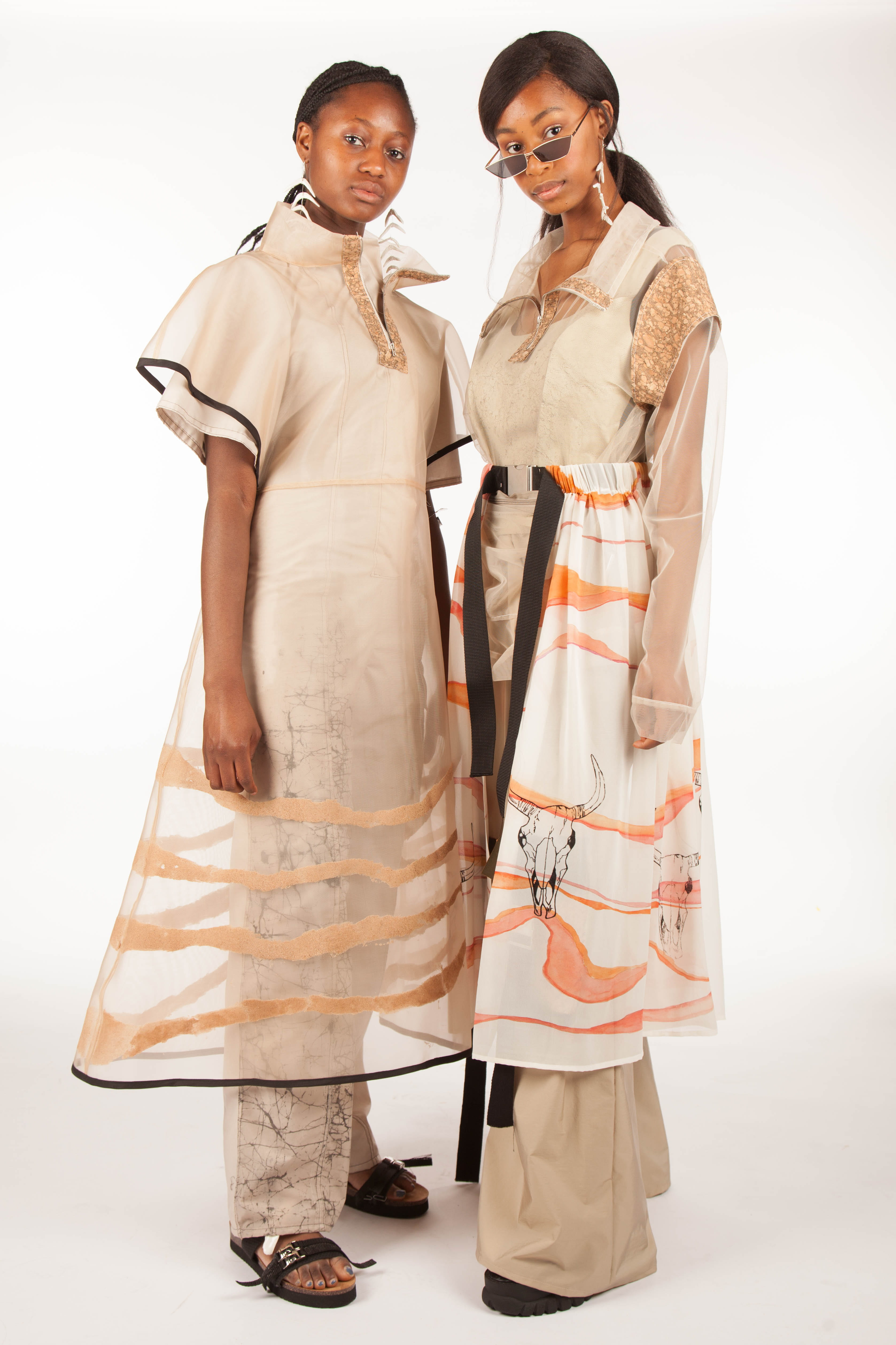 Two female models in cream and salmon dresses, each made with recycled materials.