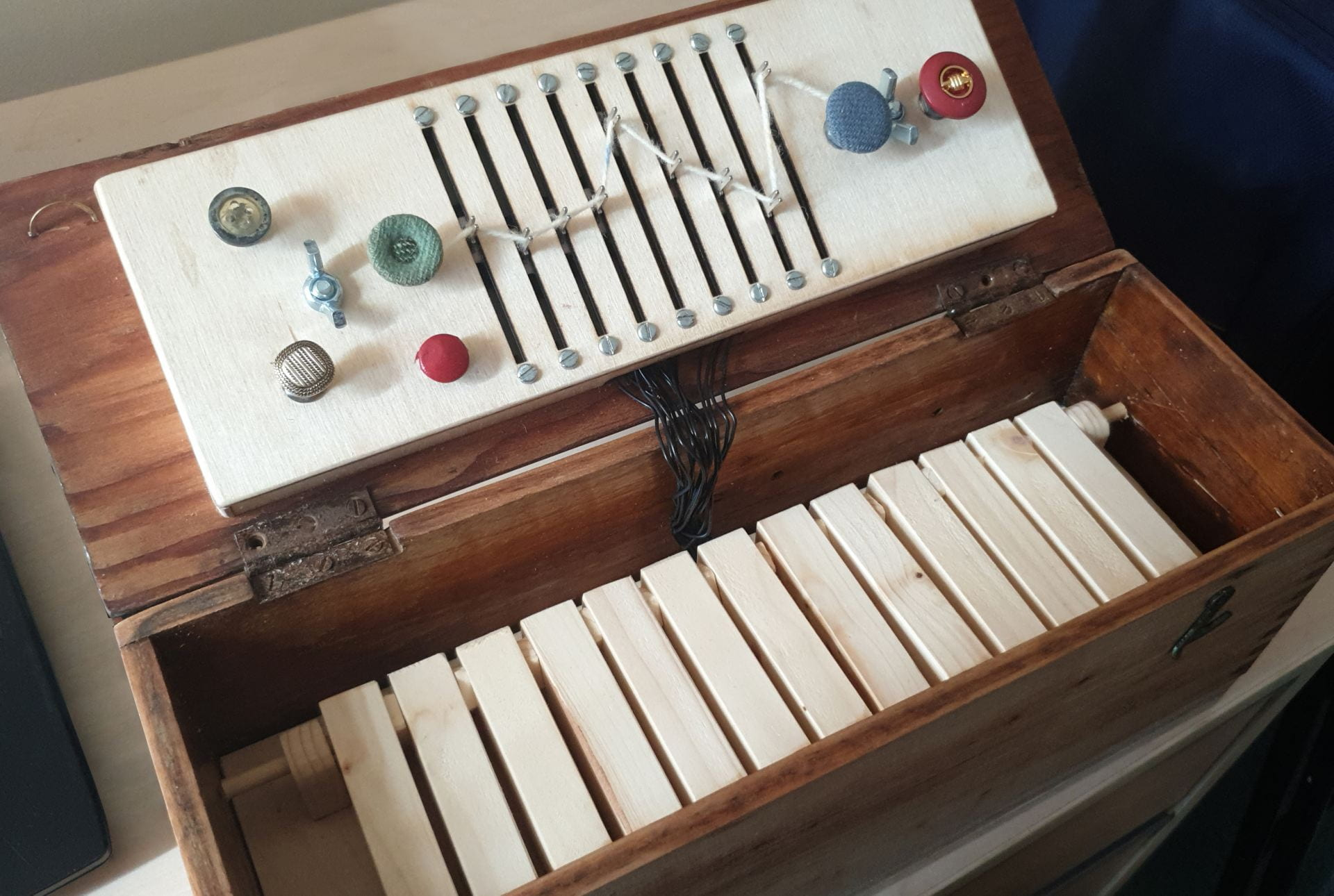 An old wooden box, with a wooden dashboard, and keys connected by wires.