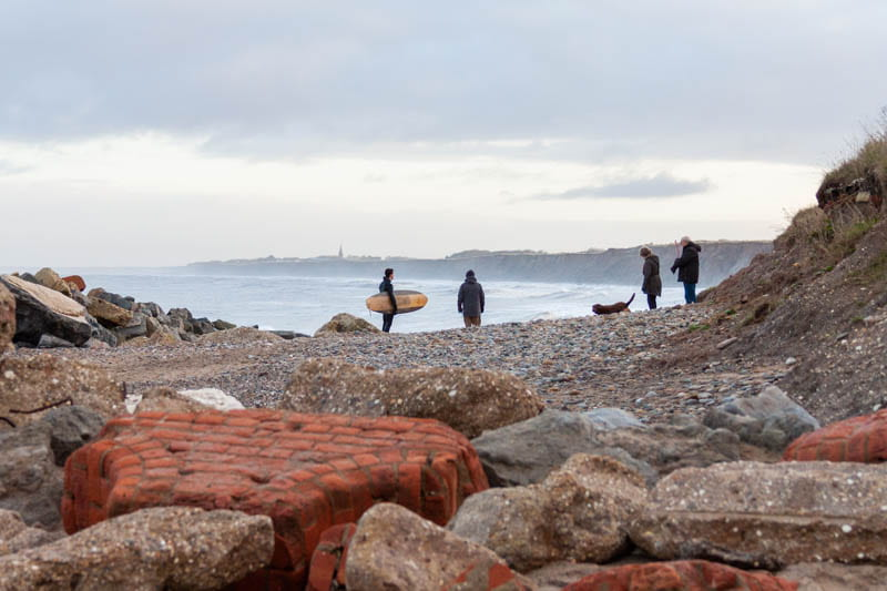 Surfer and dog walkers taking advantage of the beach, Hornsea.