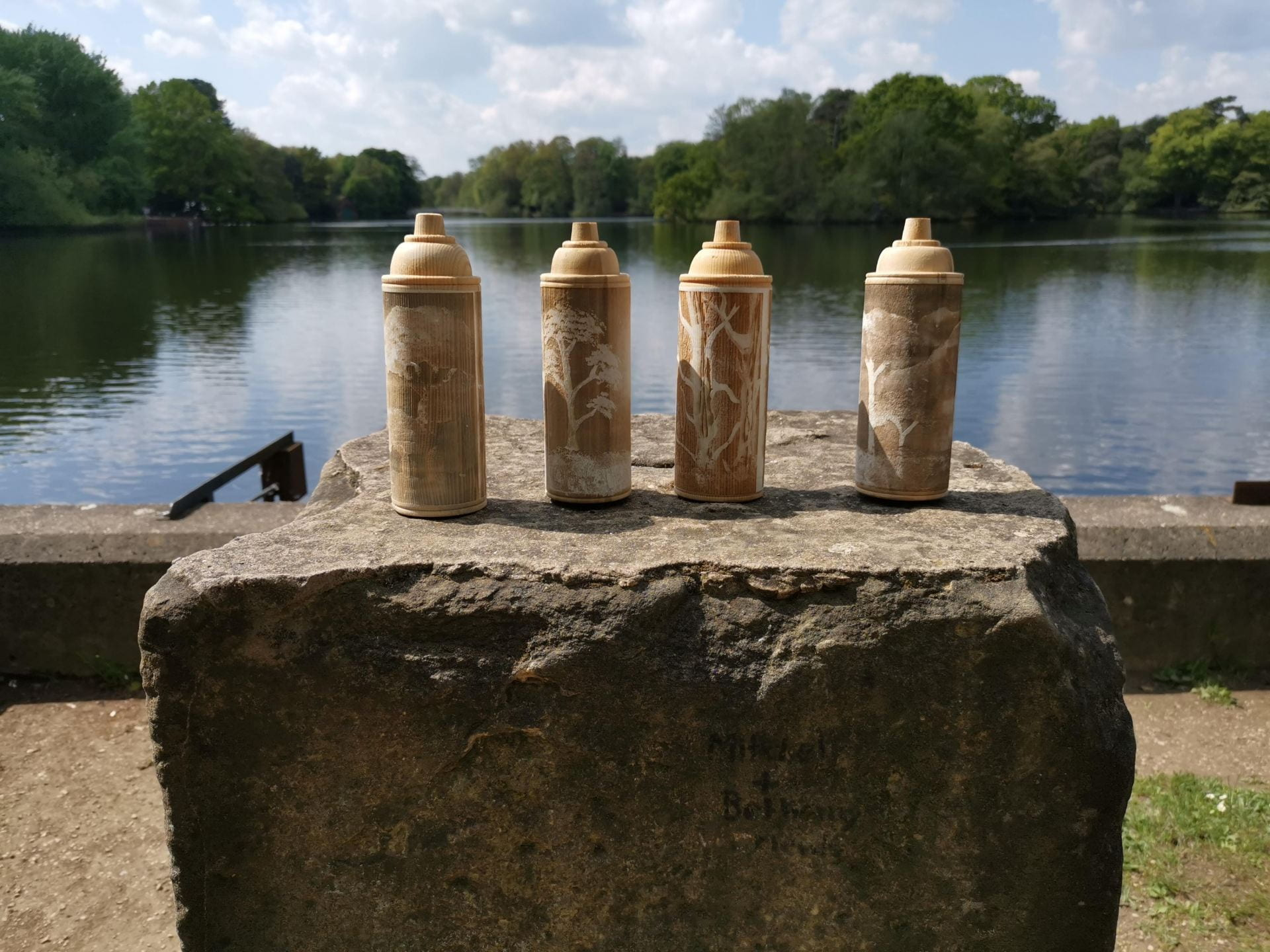 Four wooden spray paint cans on a rock, a lake in the background, each can has trees engraved into them.