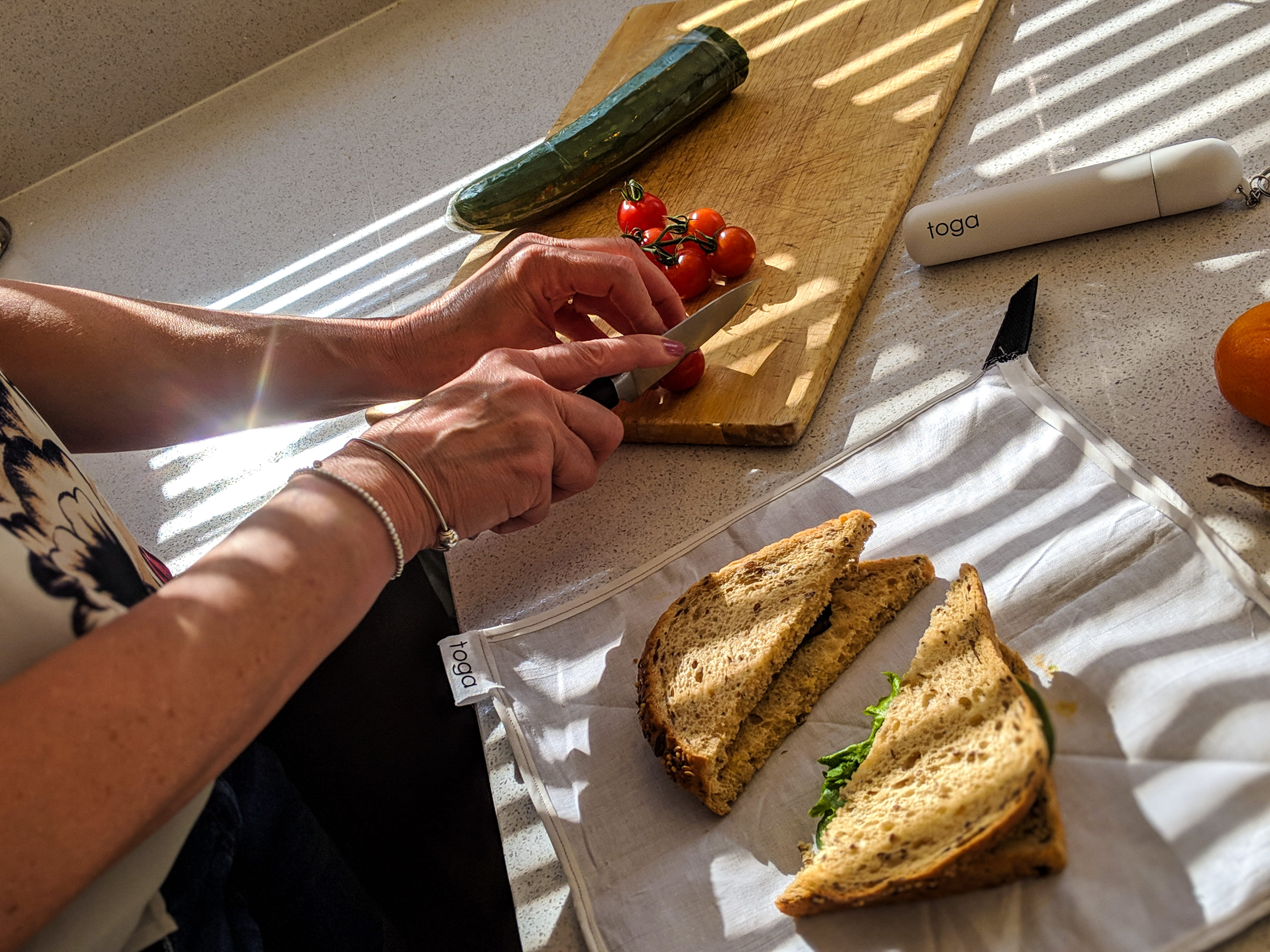 Vegetables being cut on a chopping board, with a cut sandwich and the Toga on the counter.
