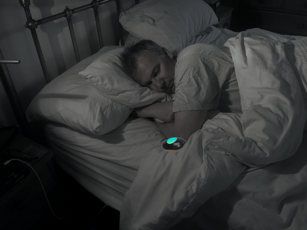 Person lying in bed with the Pebble next to them.