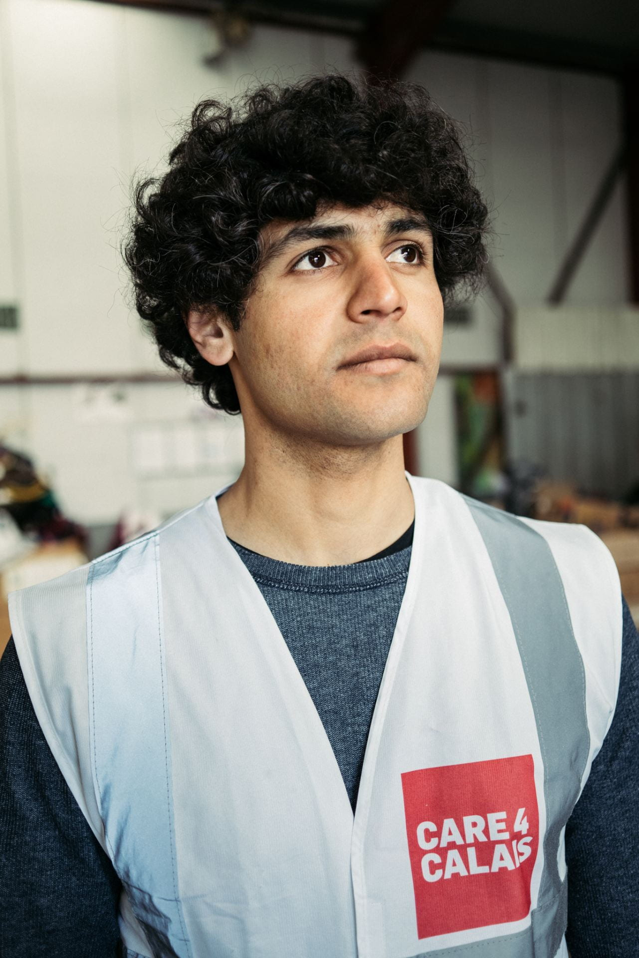 Portrait photograph of volunteer wearing off-white high visibility 'Care 4 Calais' vest.