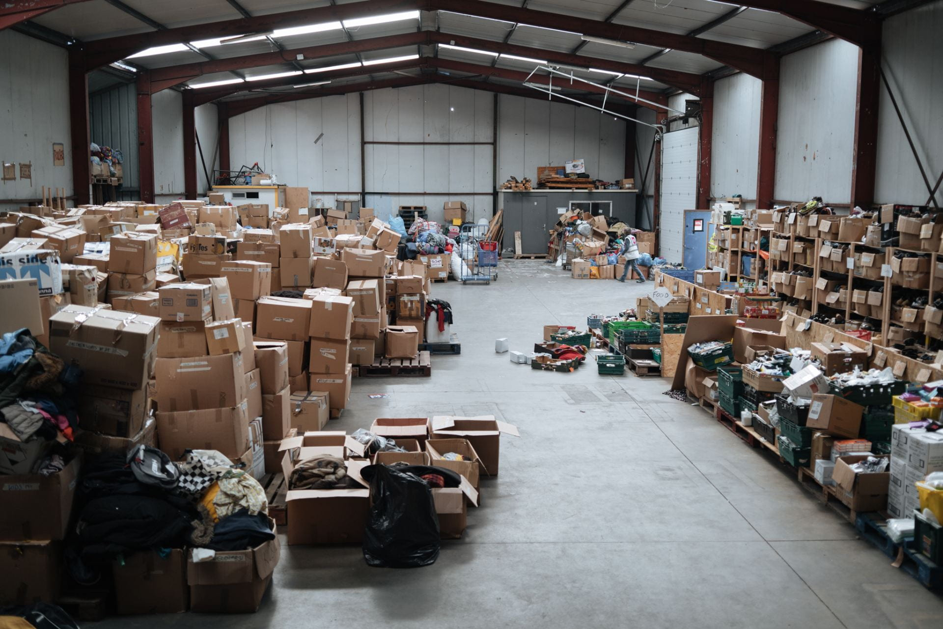 Warehouse interior, stacked cardboard boxes containing a variety of shoes & clothing.