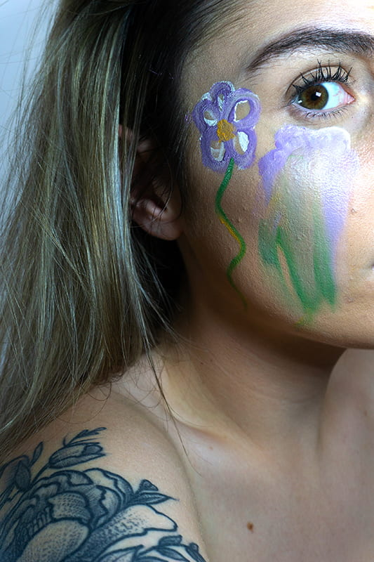 Model with a flower painted on the side of face.