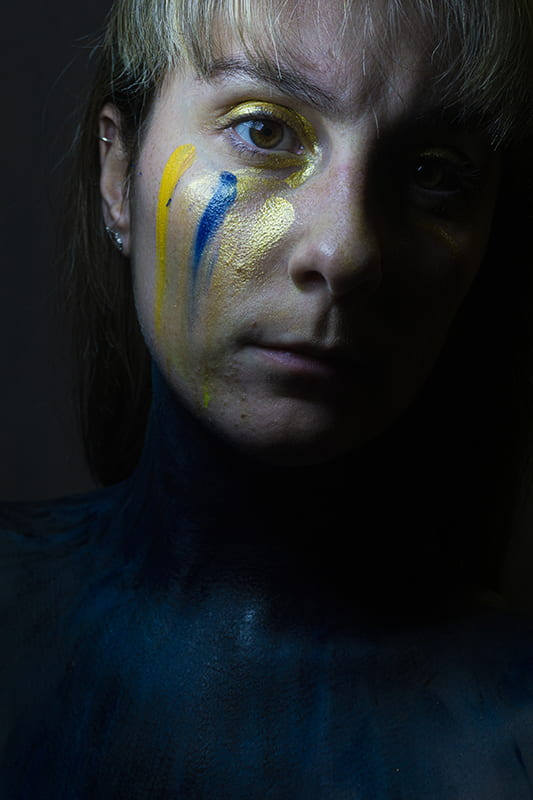 Model with yellow, gold and blue paint on face.