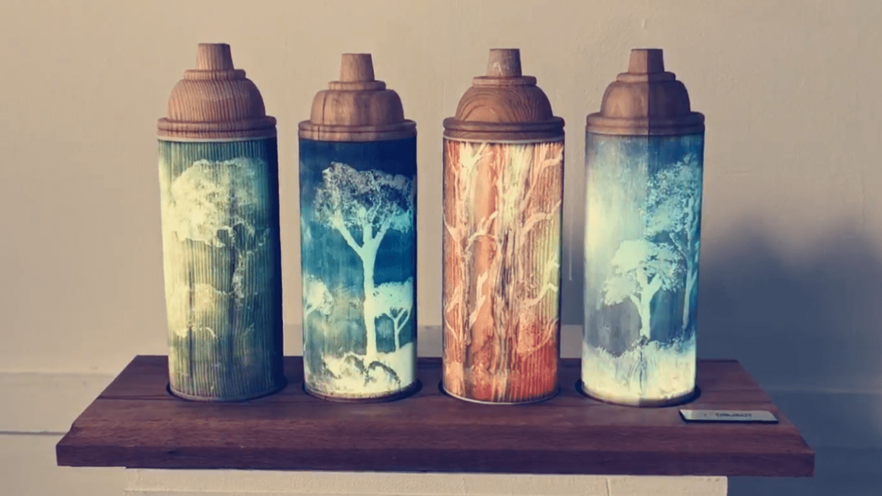 Four wooden spray paint cans on a shelf, images of tress are engraved into them, each can is a vivid colour.
