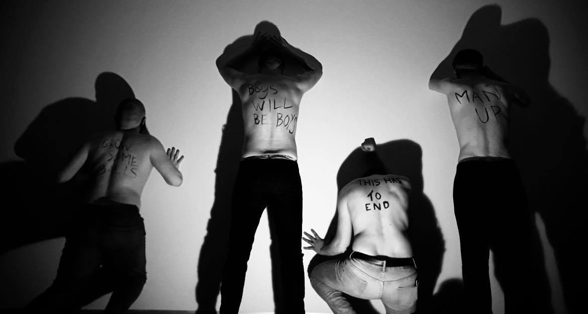 4 men stood pushing against a wall in a line, they have writing on their backs which include