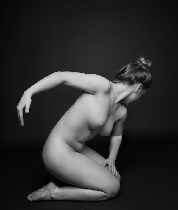 Black at white photography of nude woman in crouched ballet pose.
