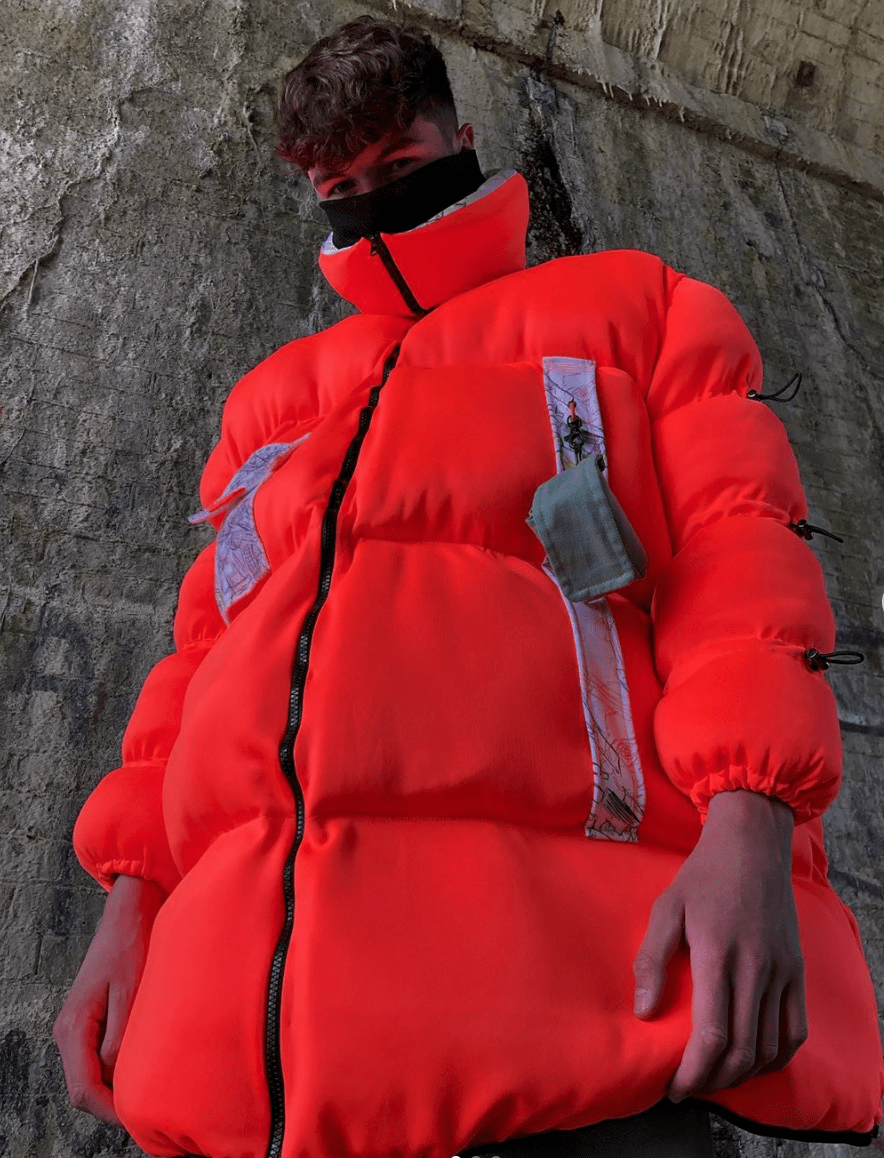 Model wearing an orange jacket that covers half his face standing next to a dirty wall.