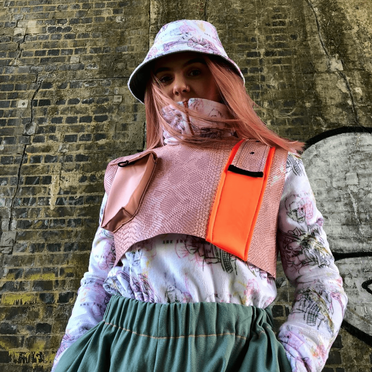 Model wearing a pink and white outfit standing next to a brick wall.