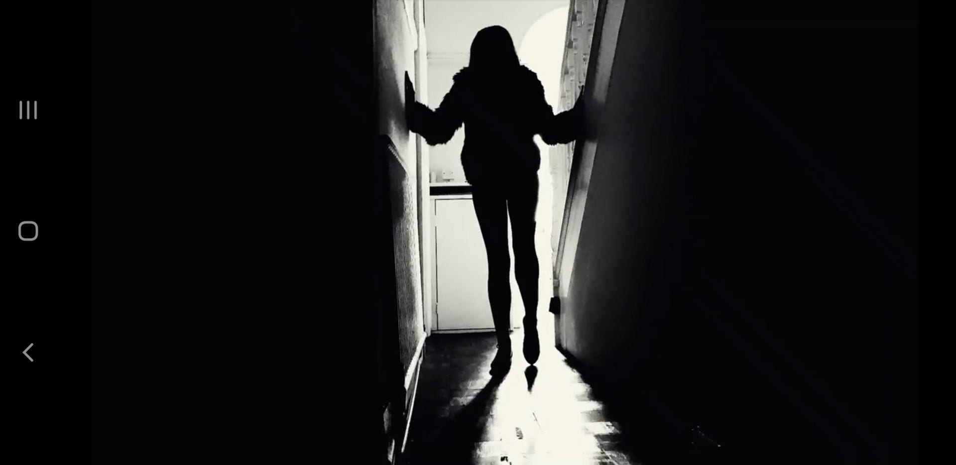 Black & white image of a person walking down a hallway.