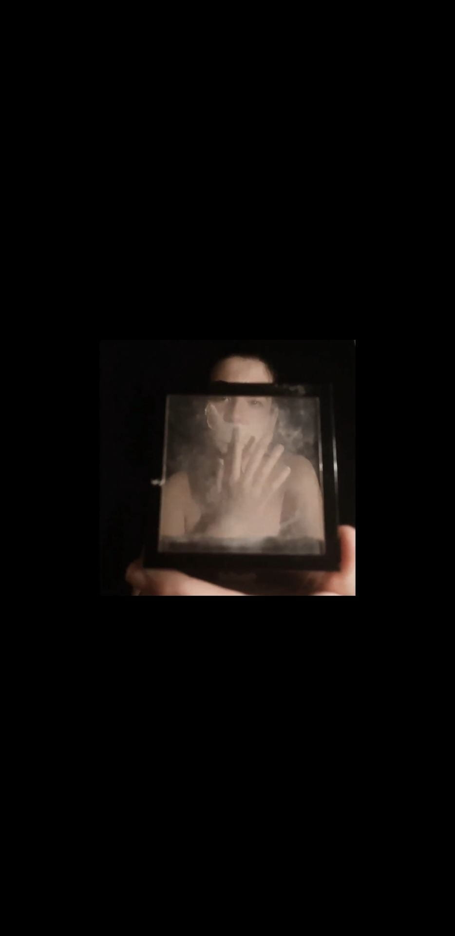 Someone holding their hand in front of their face, shot through a piece of glass.