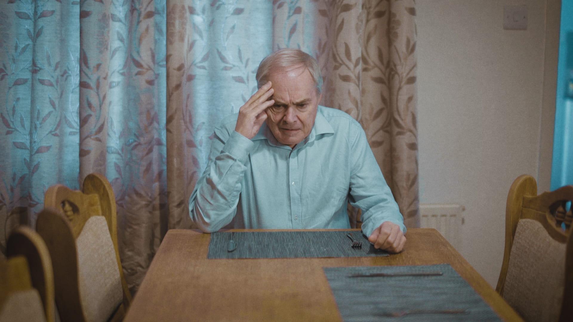 Man, upset, sat at kitchen table.
