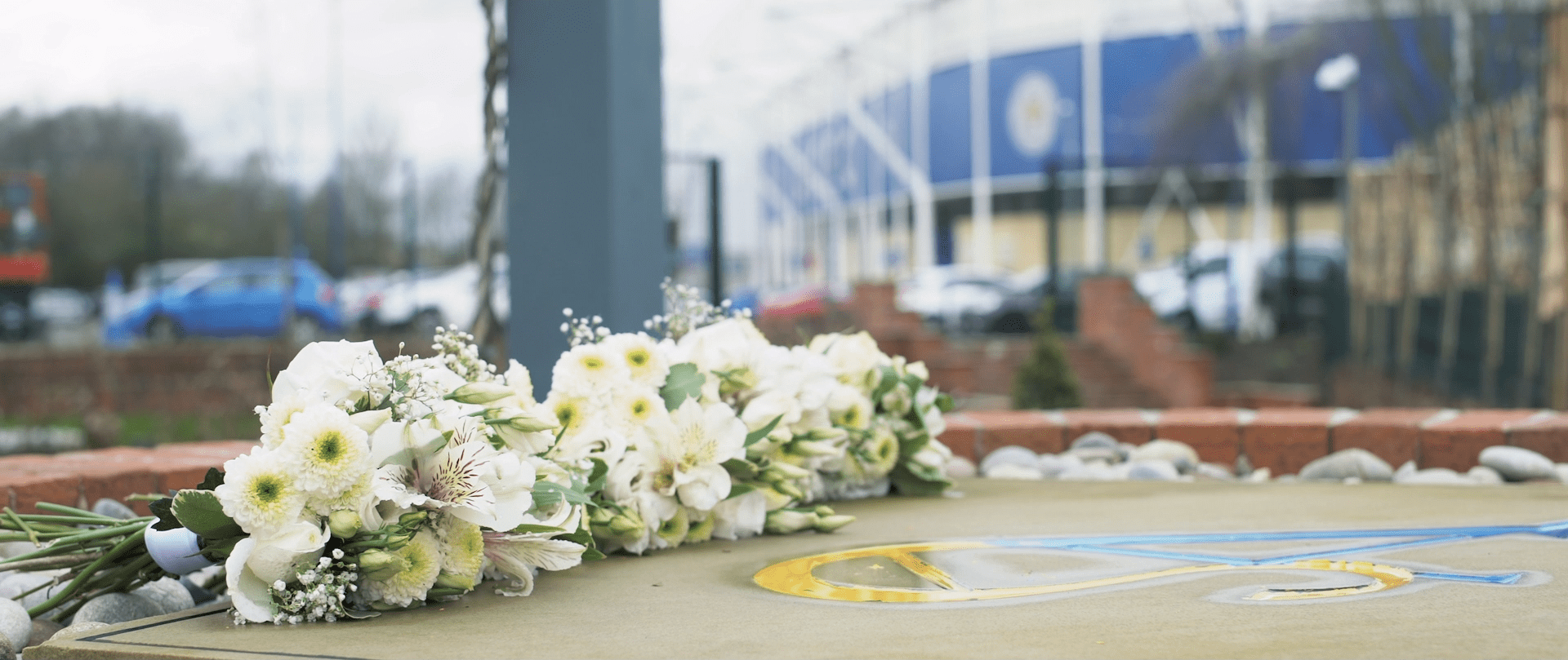 Flowers laid on the floor outside Leicester City Football Stadium.