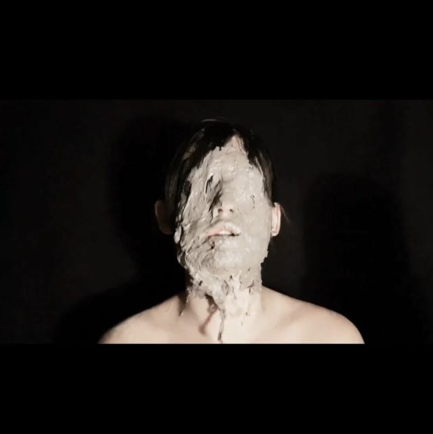 Photograph of a person with clay all over their face.