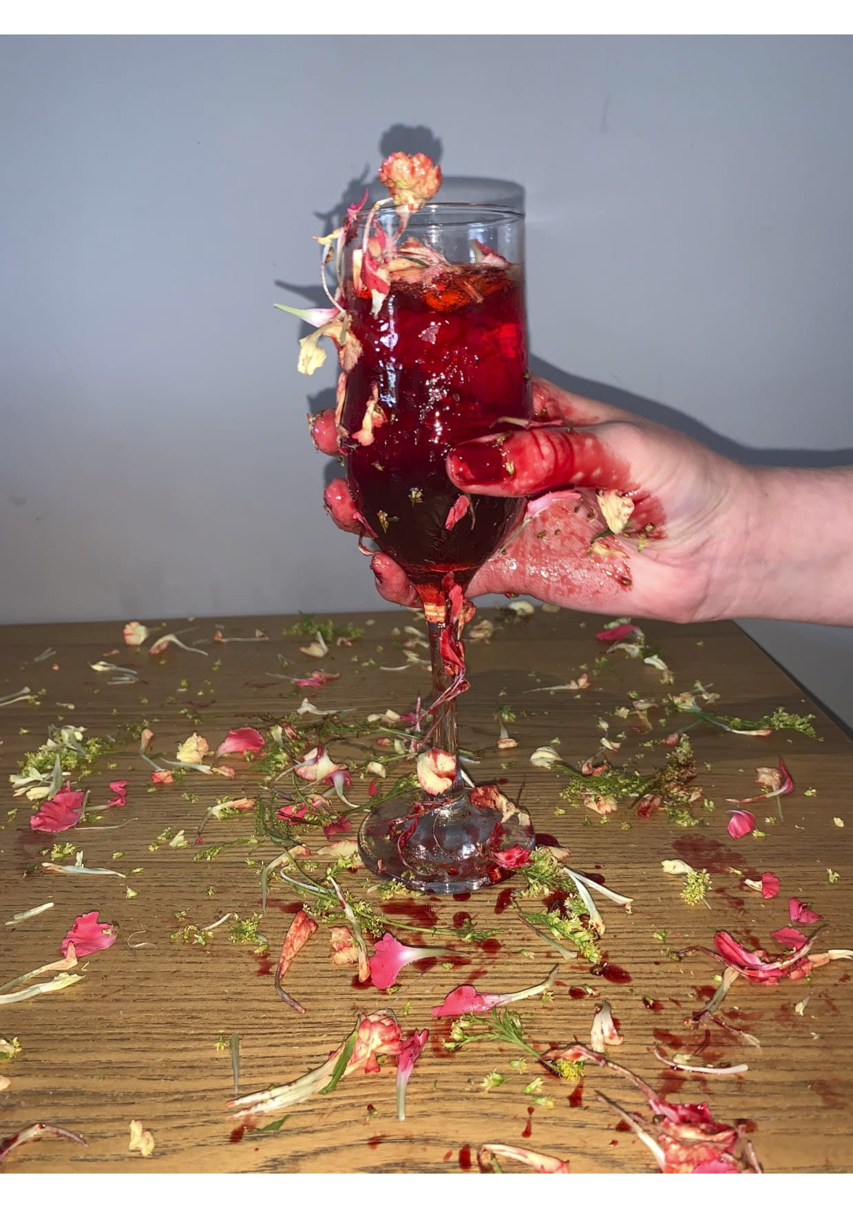 Hand holding a glass full of flowers and red liquid.