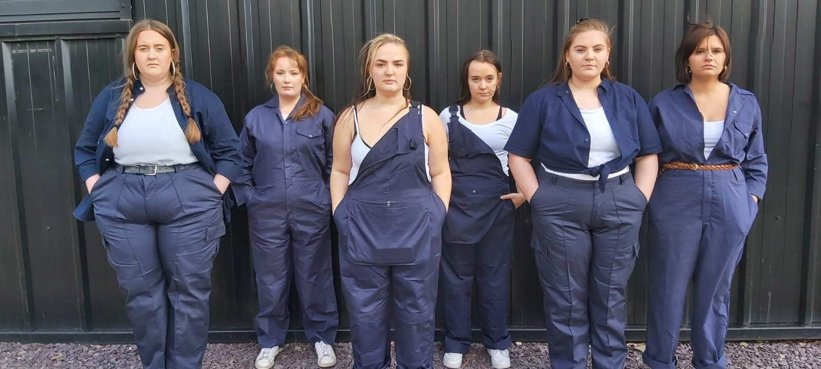 Image contains six women standing face on to the camera, looking serious. All dressed in men's workwear.