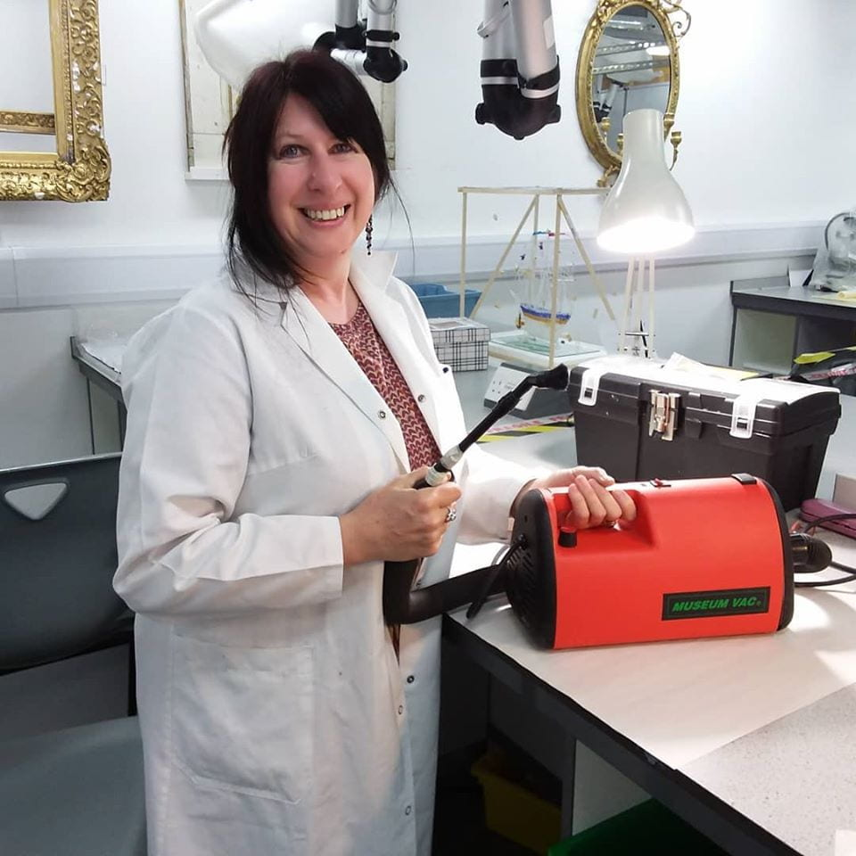 Conservator with tapestry cleaning equipment in laboratory.