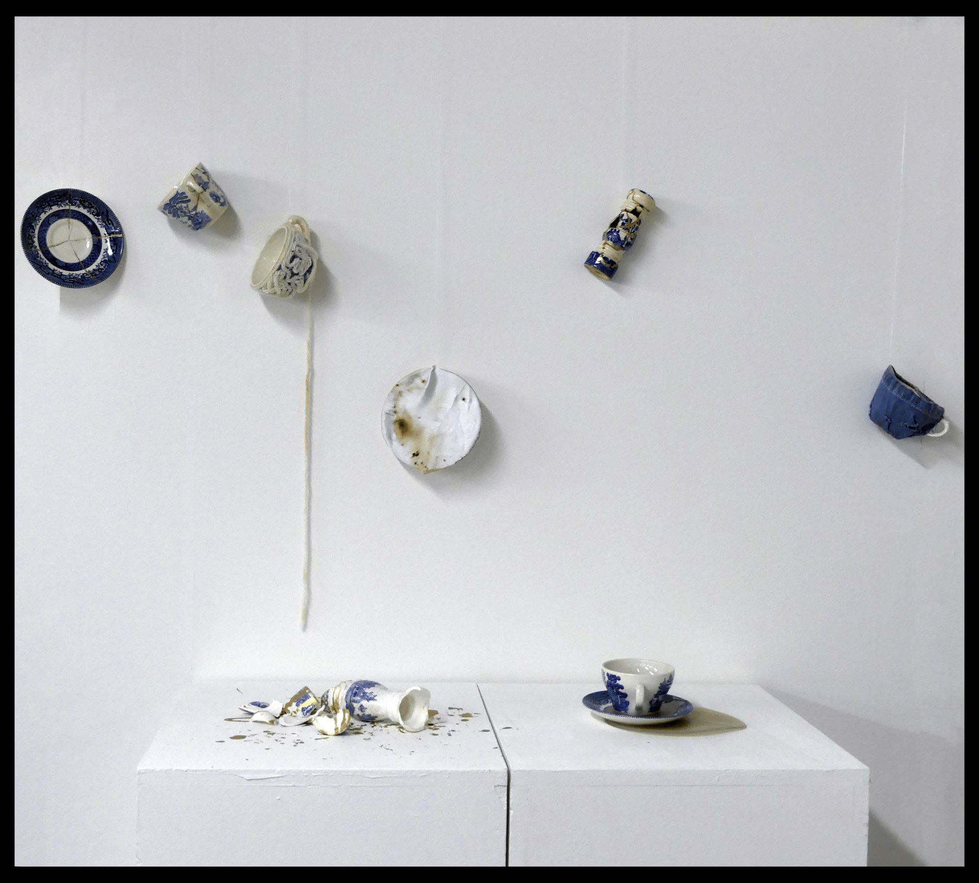 Artistic piece named 'Peace of Mind' a solo installation piece which explored control and the anxieties I experience when having no control over my environment, featuring blue and white crockery either smashed or in mid air.