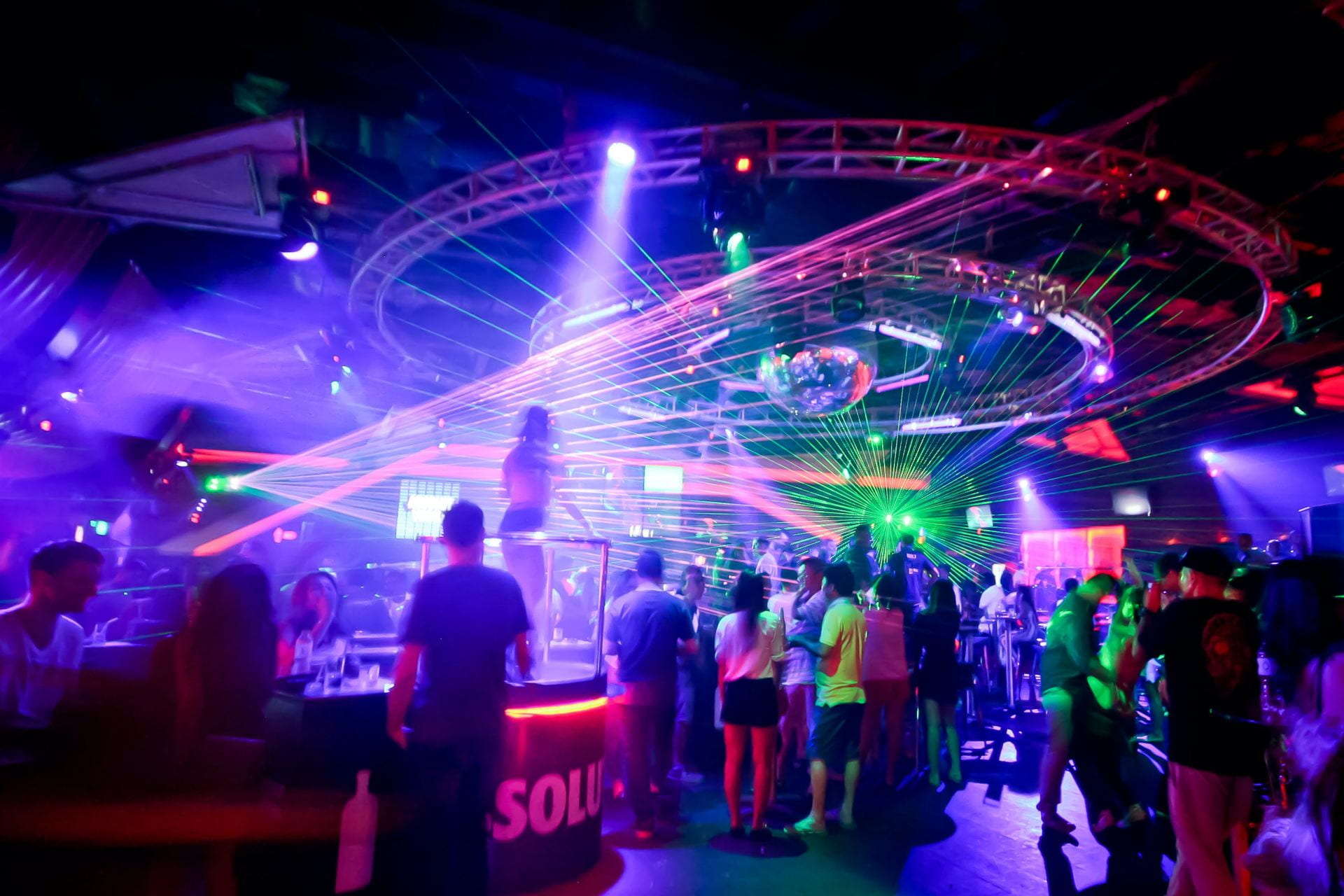 Crowded nightclub featuring strobe lights.