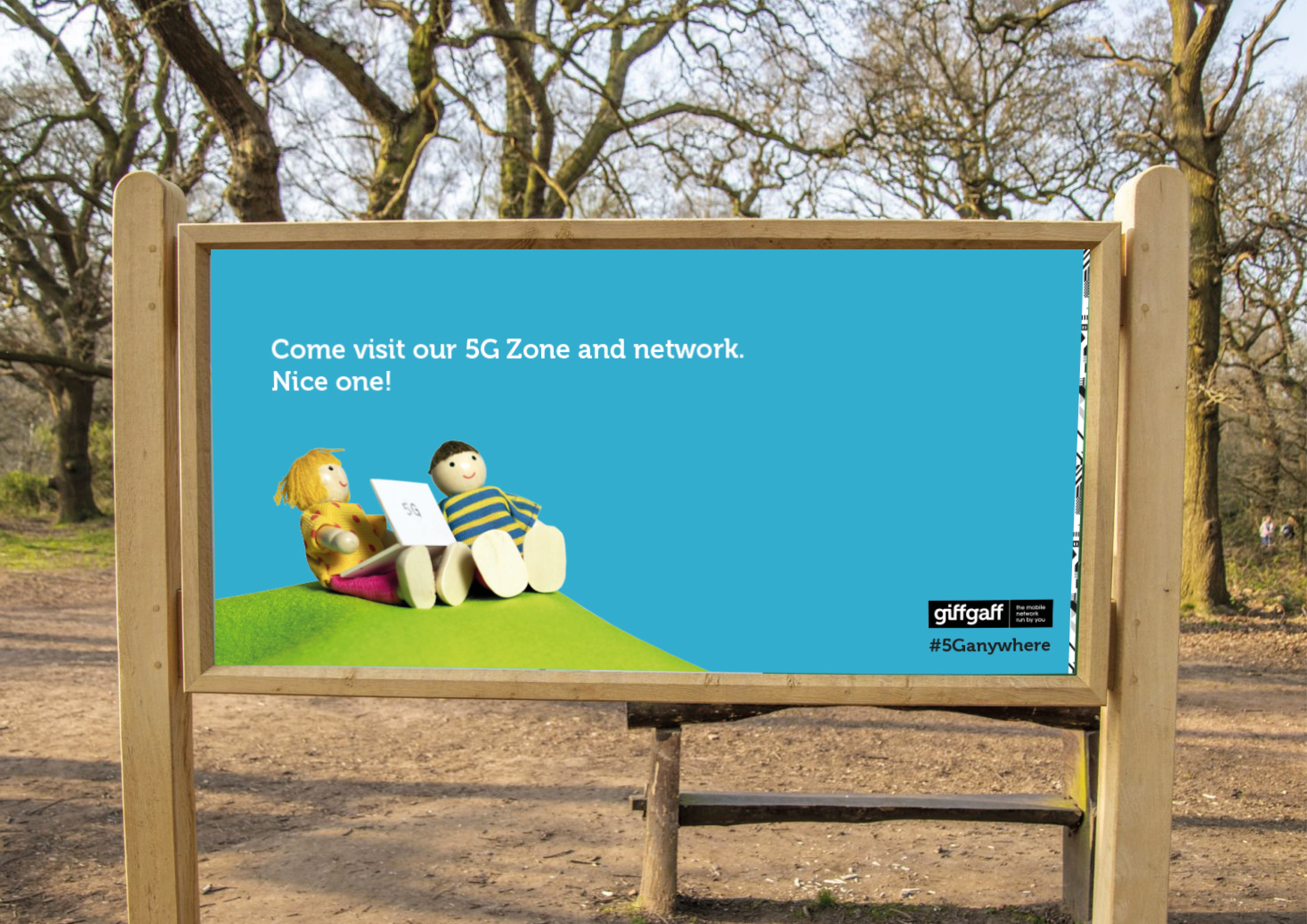 Photograph of a a sign in a park with posters for giffgaff.